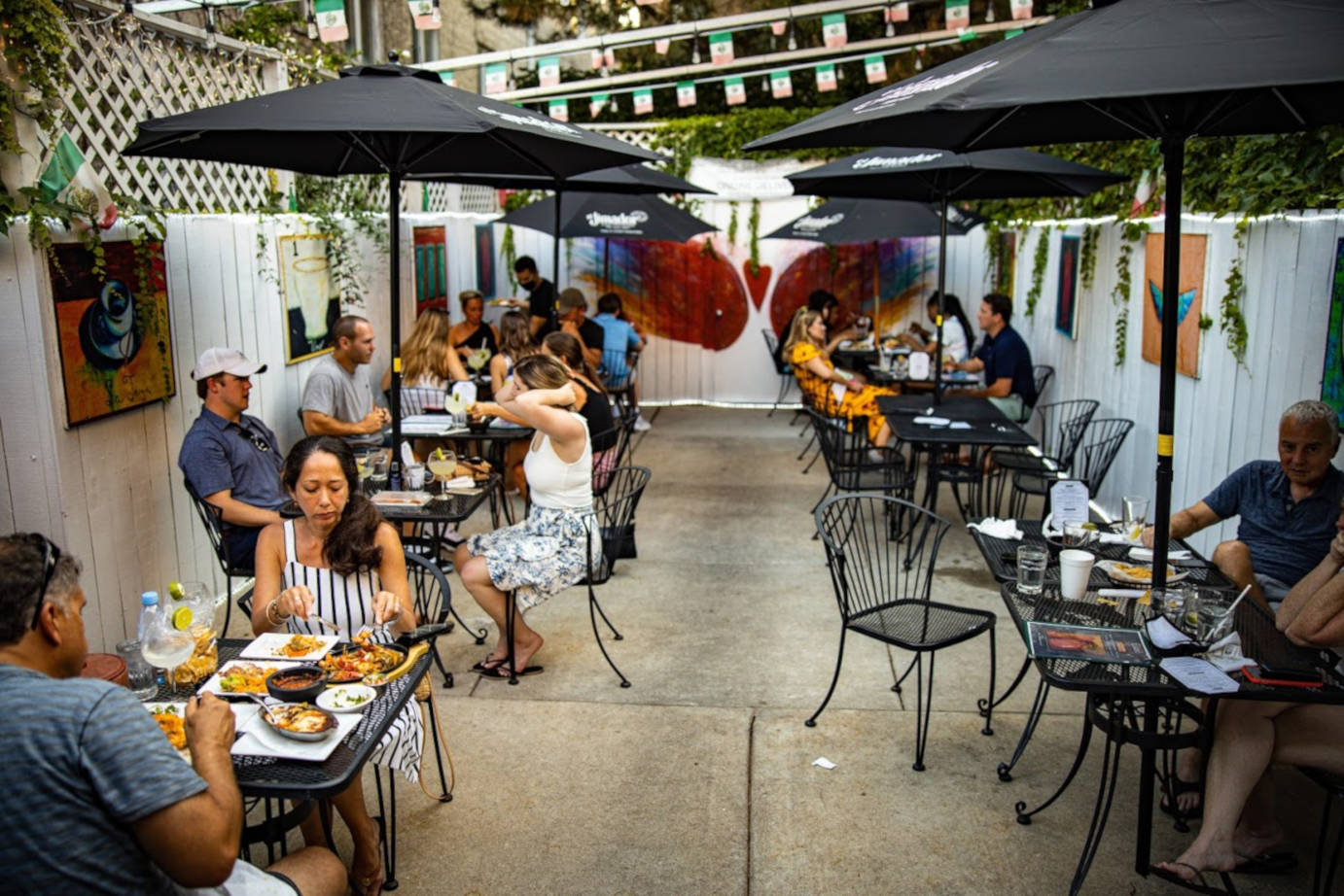 Exterior, tables lined up, guests enjoying food and drink