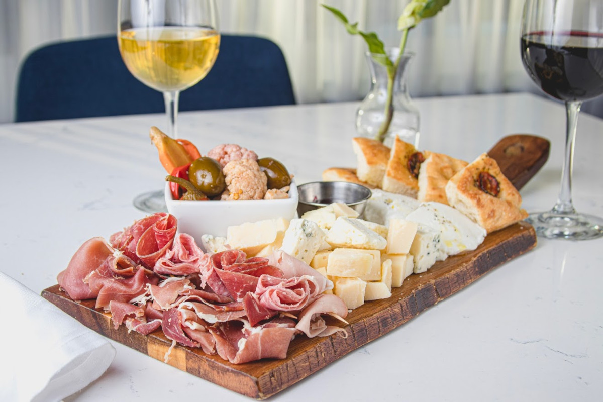 Smoked meat, cheese, snacks and glasses of red and white wine on the side