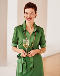 a woman in a green dress holding a glass of white wine