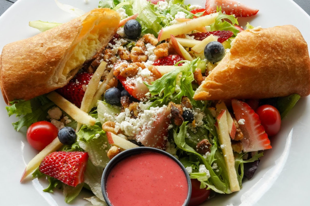 Mixed salad with pastry, vegetables and fruit, dip on the side