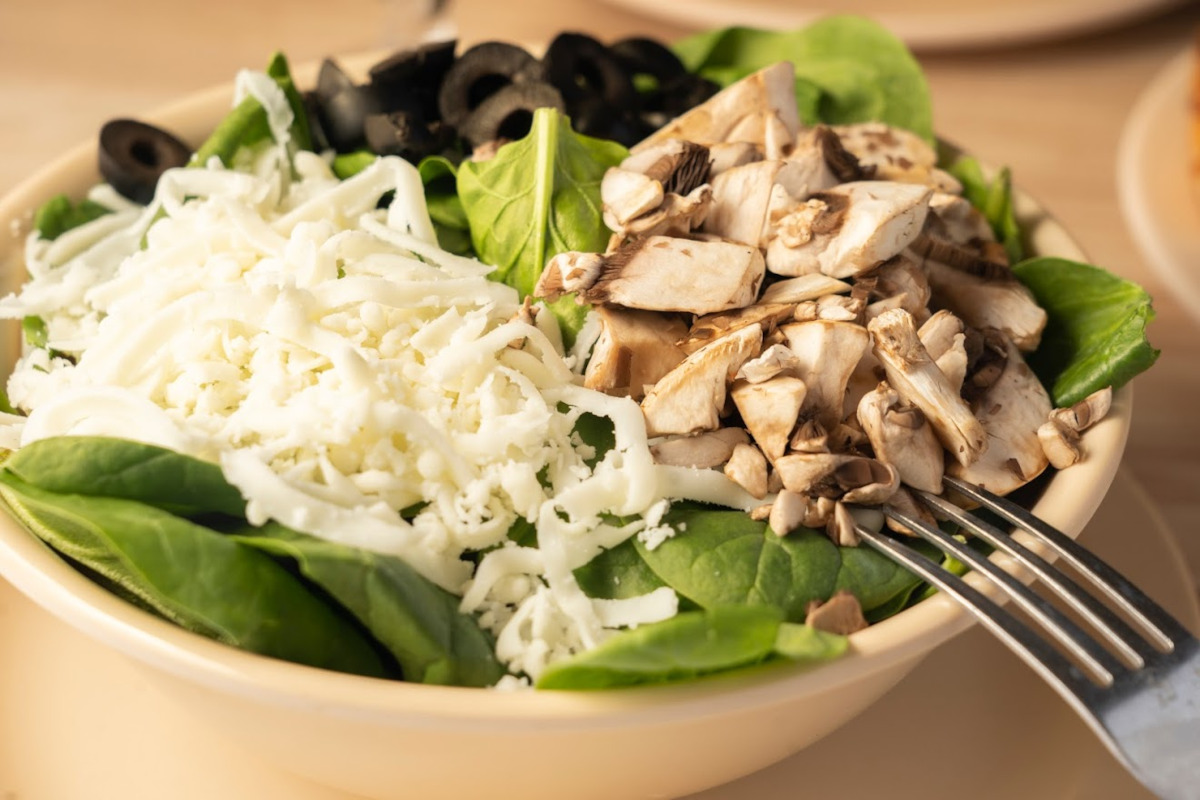 Spinach salad topped with mushrooms, black olives and mozzarella cheese