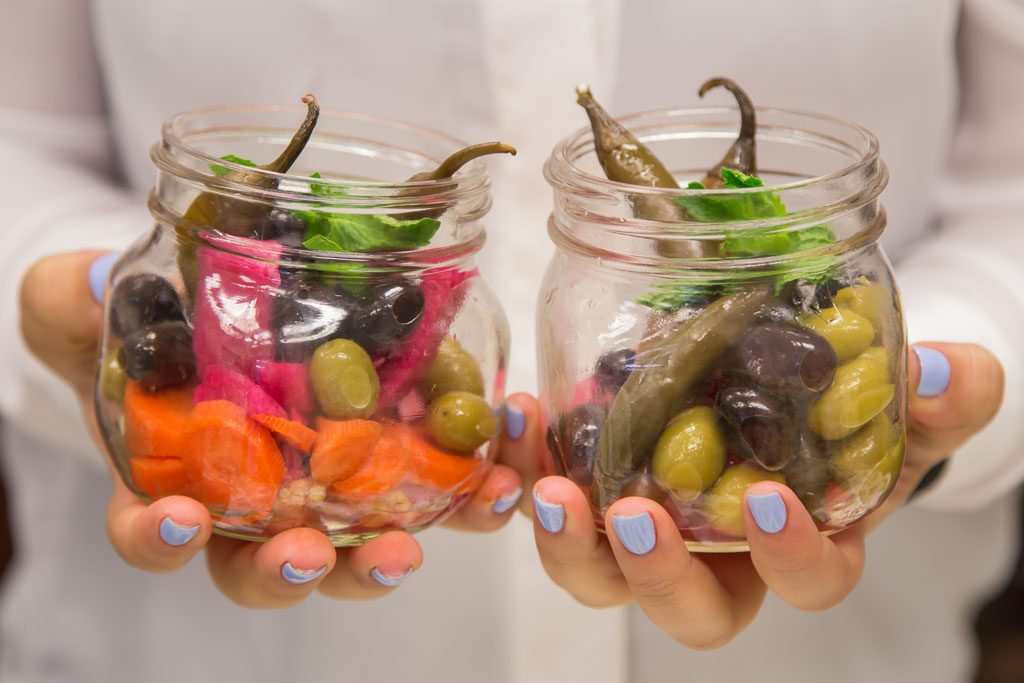 A person holding two jars with pickled vegetables