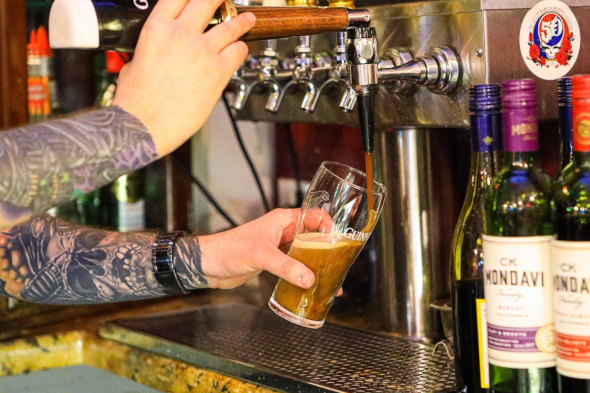 Staff member pouring beer
