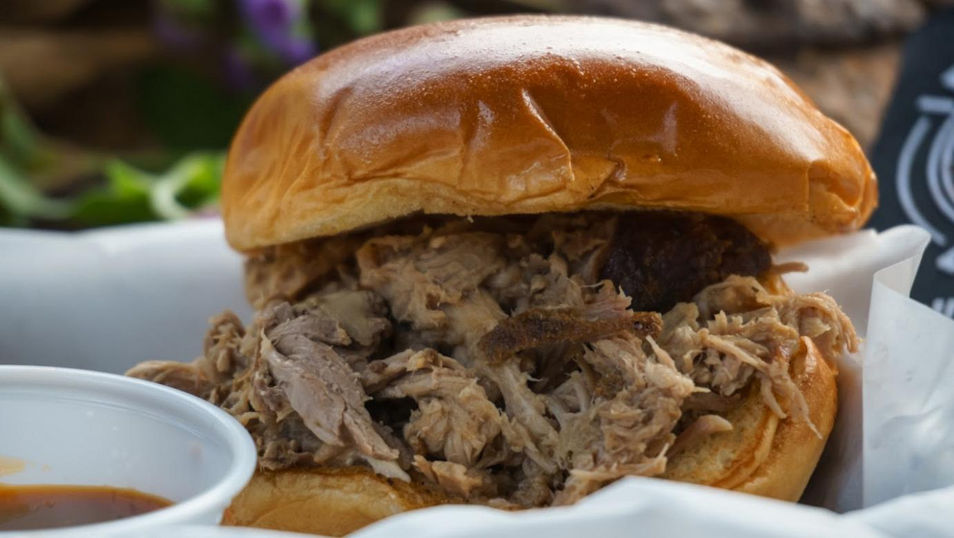 smoked pulled pork is served on a Brioche bun with a garnish of house-made slaw