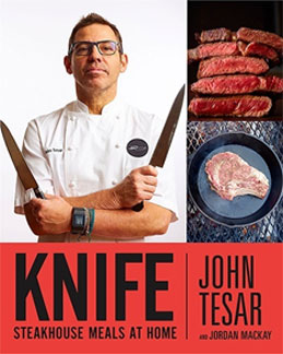 Chef John Tesar holding two knives