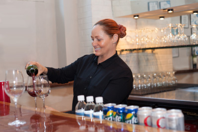 Staff member pouring a glass of wine