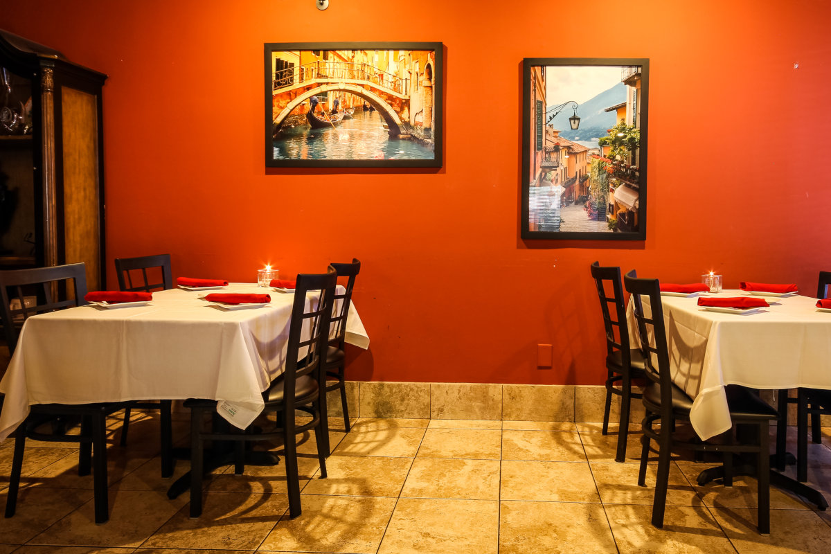 Interior, two tables for four, pictures on the wall in the back