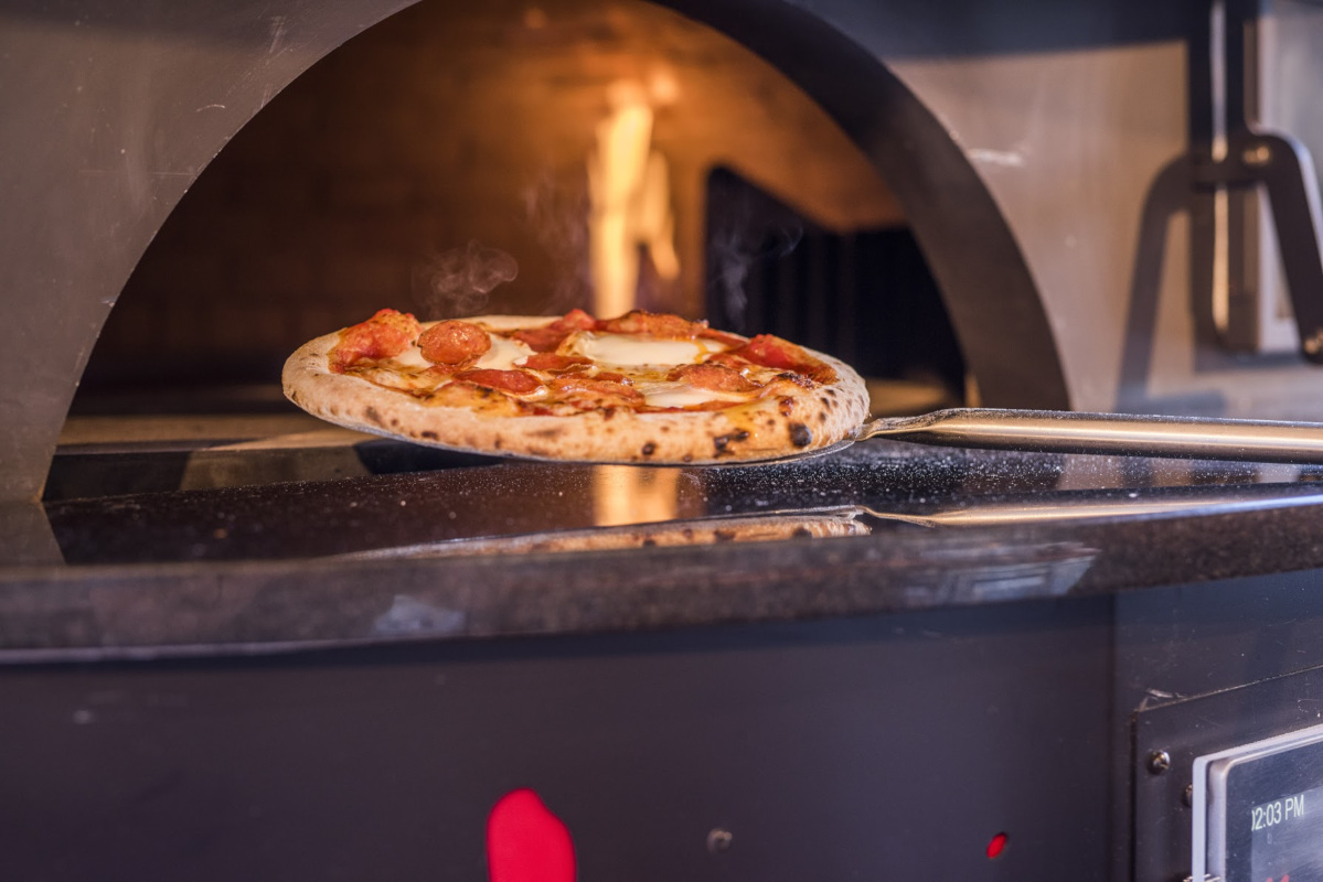 a pizza on top of a stove in a kitchen