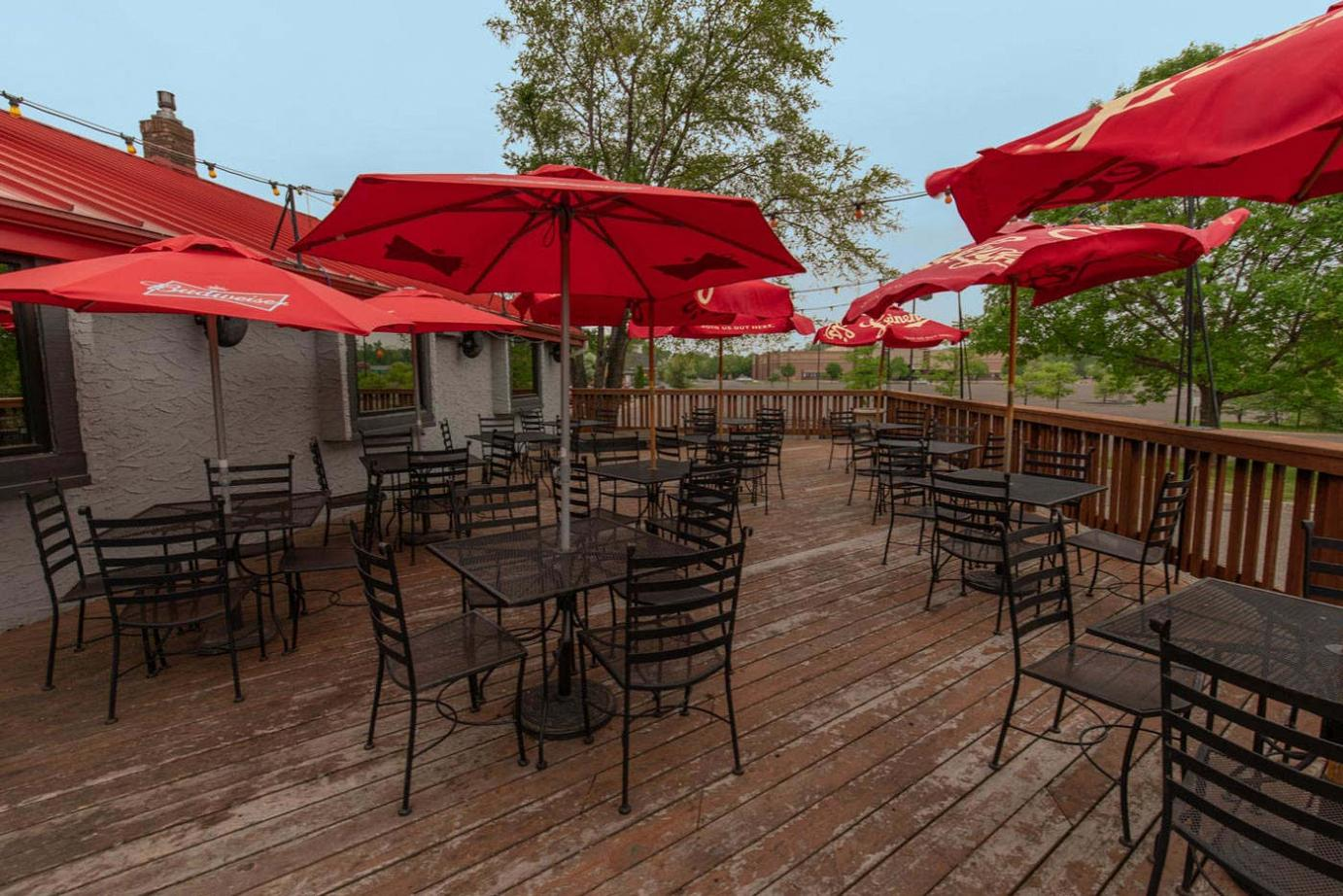 wooden patio, red parasols, black chairs and tables