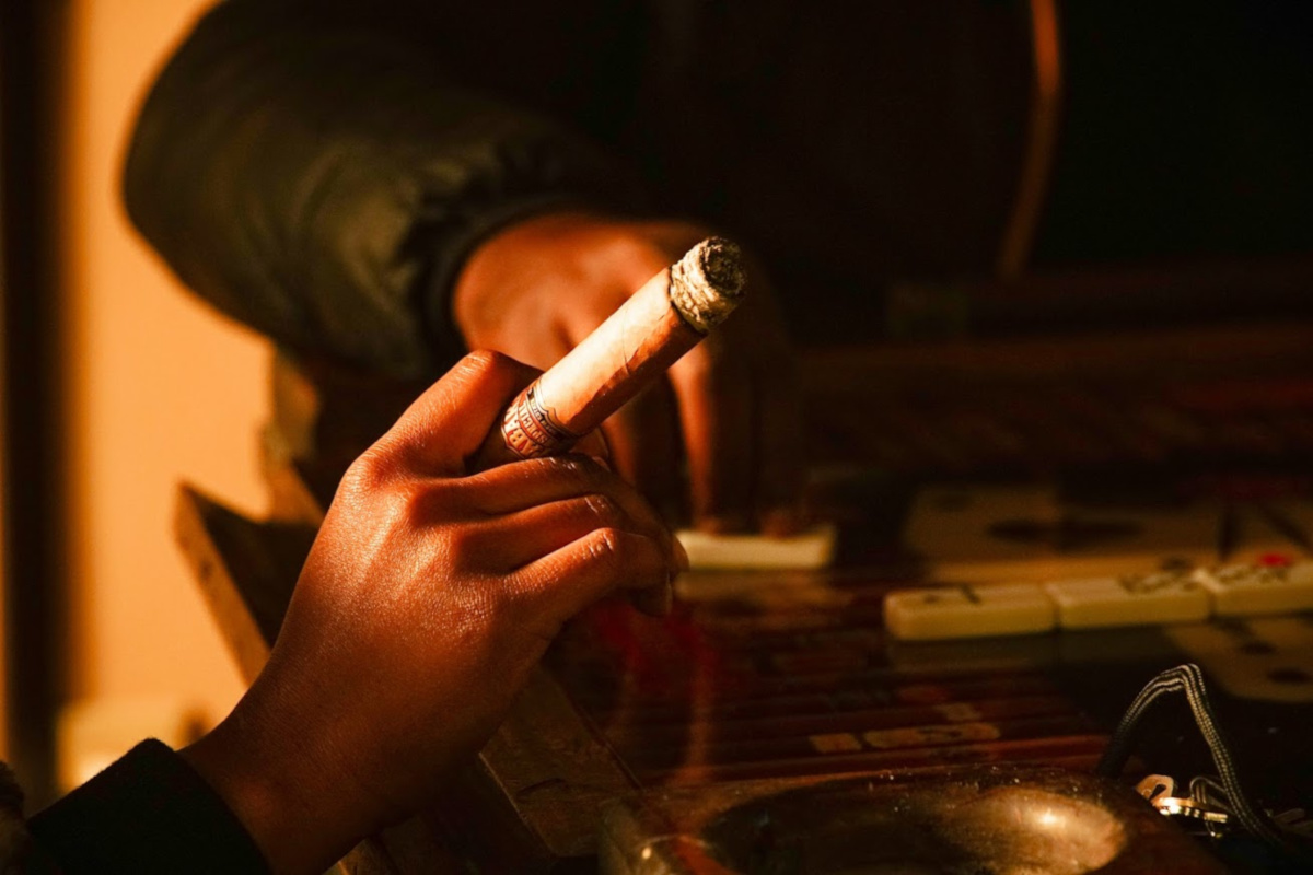 A man holding a cigar, closeup