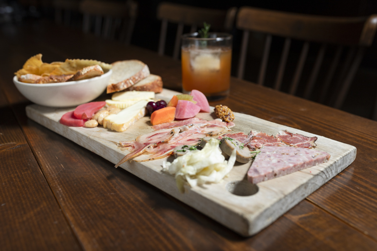 wooden board filled with cheese, bread, and meat produce