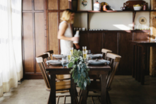 Interior, set table, woman walking by
