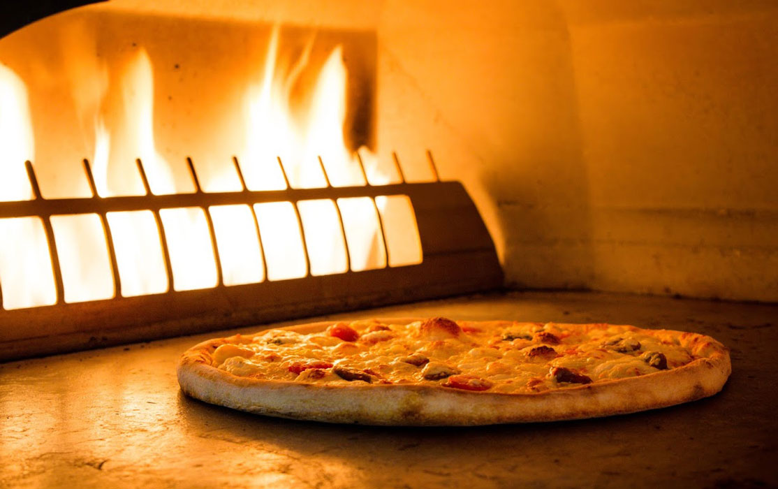pizza in front of the stone stove