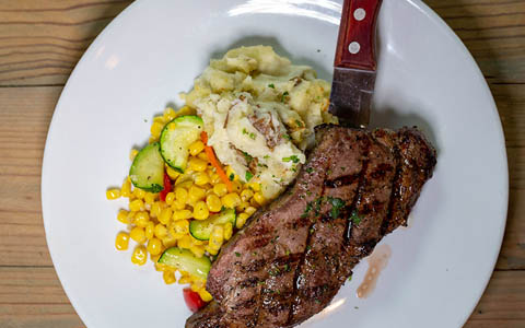 Steak with mashed potatoes and vegetables, top view