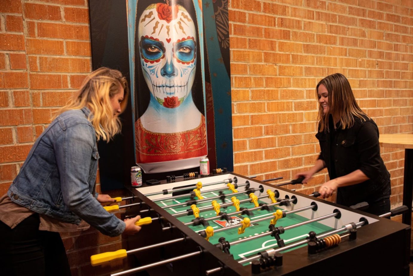 Teo girls playing table soccer, and picture on the wall,