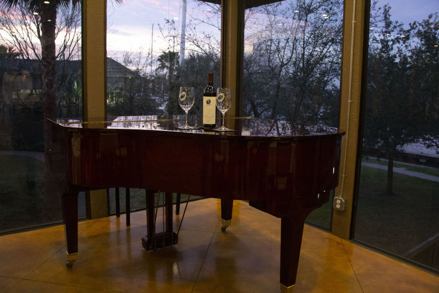 Restaurant piano, two glasses and bottle of red wine