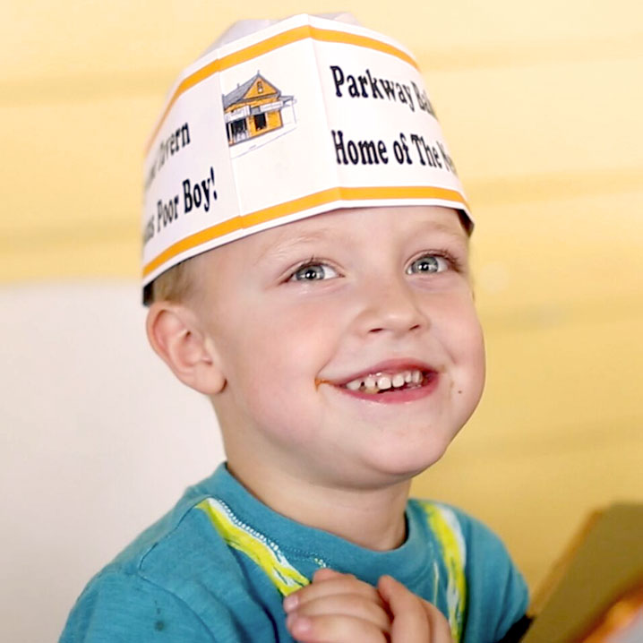 Photo of a kid with improvised hat with restaurant logo