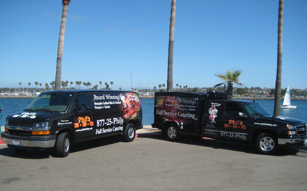 Two black vans by the seashore