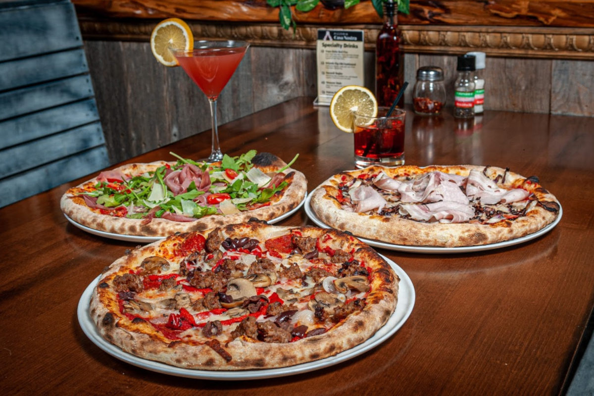 Three pizzas and cocktails on the table