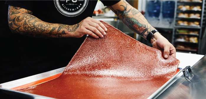 Staff member preparing a ketchup leather™