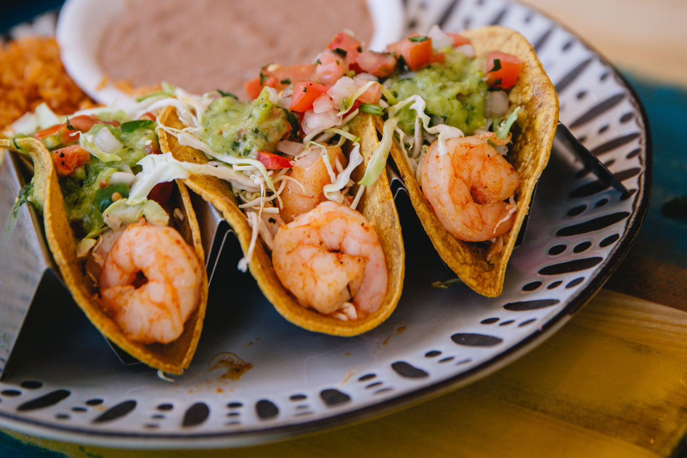 Three tacos with shrimps and salad