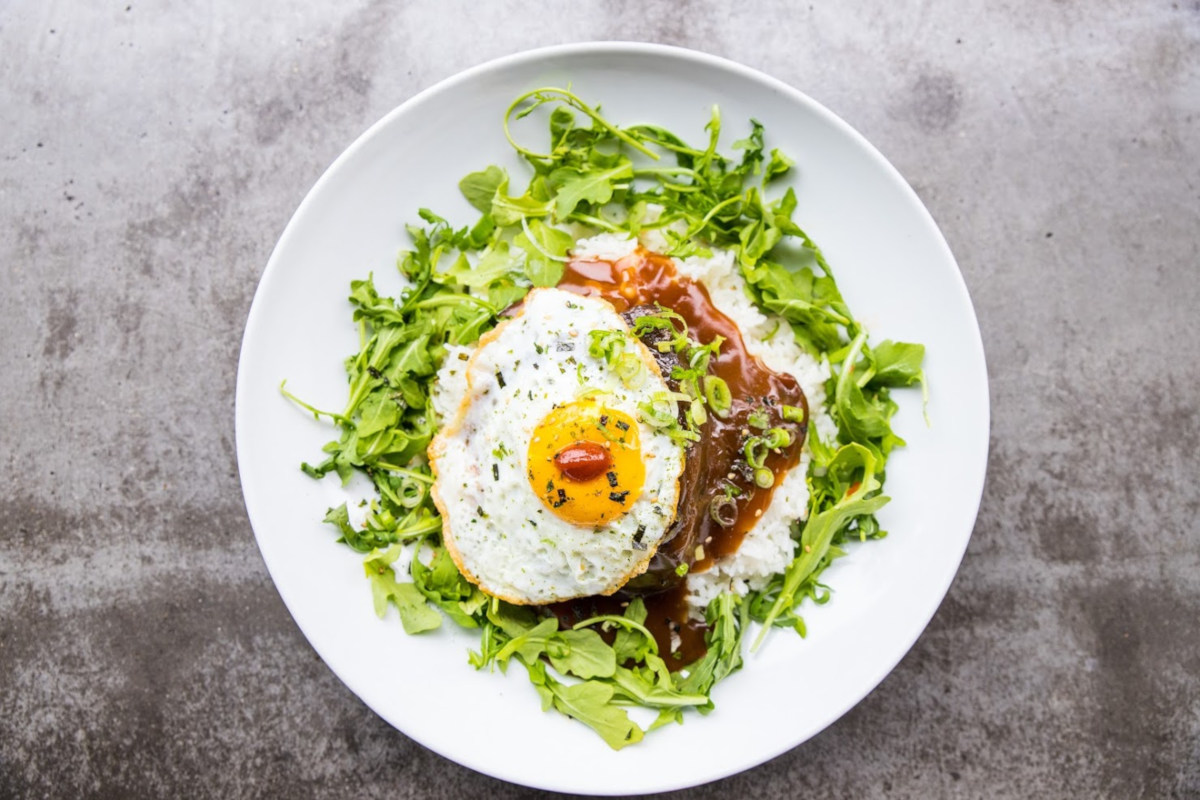 Fried eggs with sauce and green salad