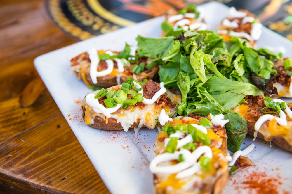 Baked potatoes with cheese, bacon, cream and greens