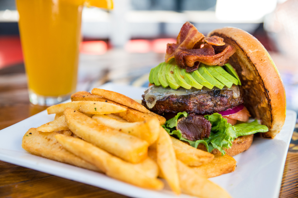 Rich avocado burger with fries and bacon