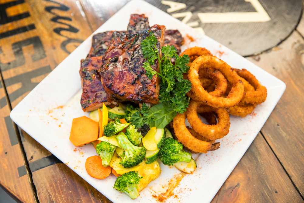 Glazed steak with onion rings and steamed veggies