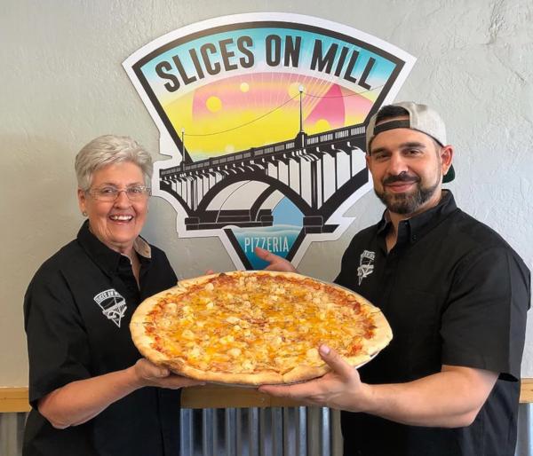 Staff members holding big pizza