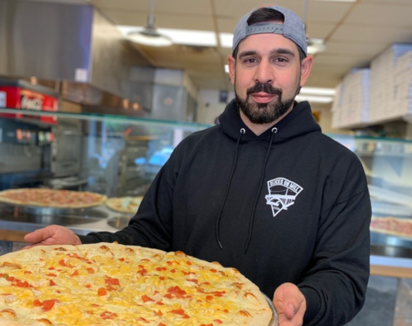 Staff member posing for a photo, holding pizza