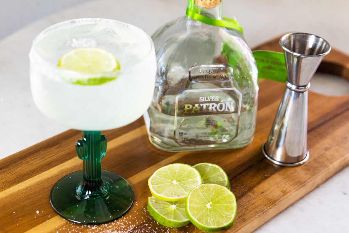 White cocktail with lime, a bottle and a cocktail measuring cup