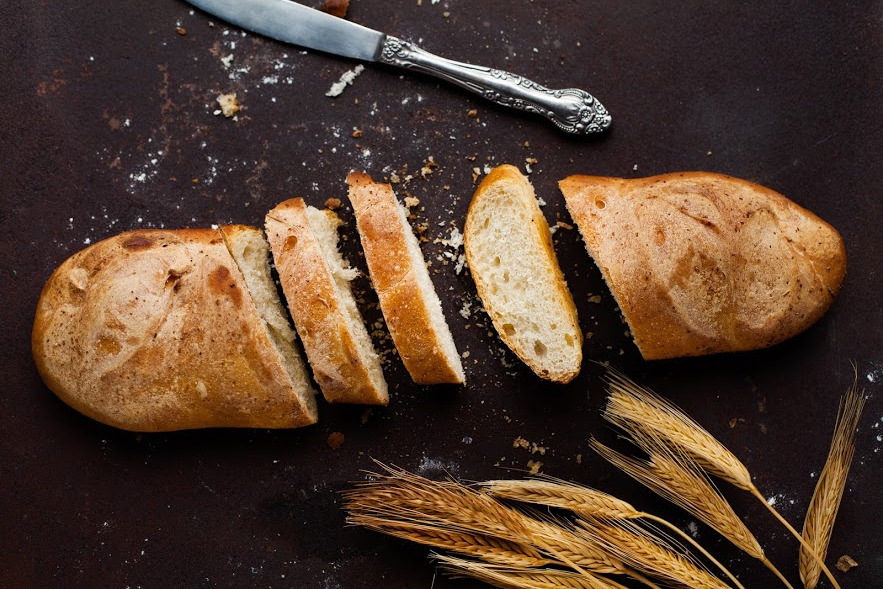 Wheat, knife, and bread on the table