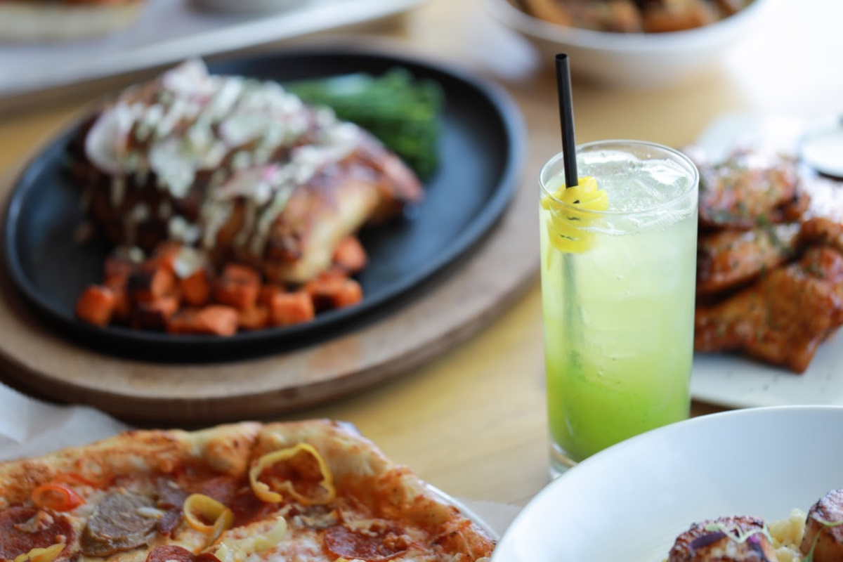Various dishes and glass of lemonade, closeup