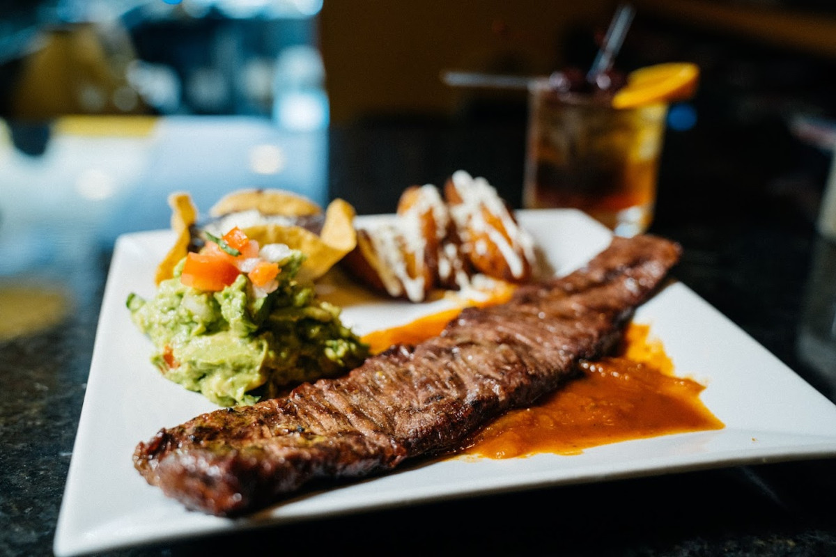 Skirt Steak marinated and broiled, served with fried plantains,