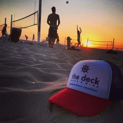 people playing vleyball on the beach, deck red white and blue hat
