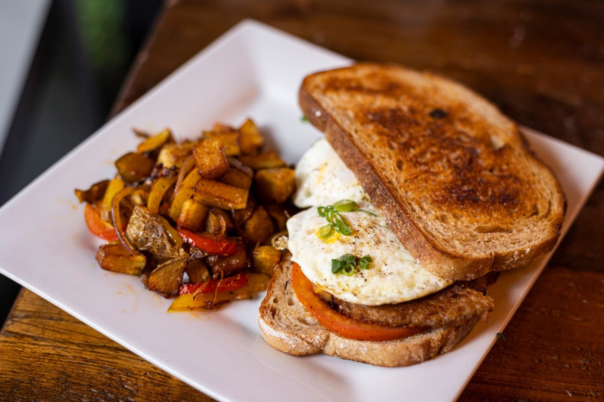 Sandwich with meat, tomato and fried egg, baked potato on the side