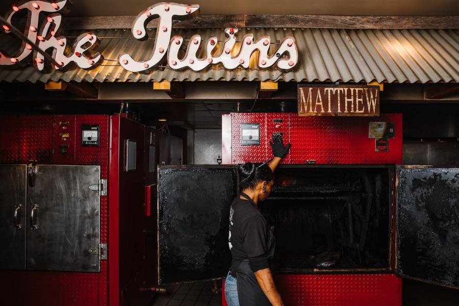 Restaurant interior, red smokers, restaurant logo above the door