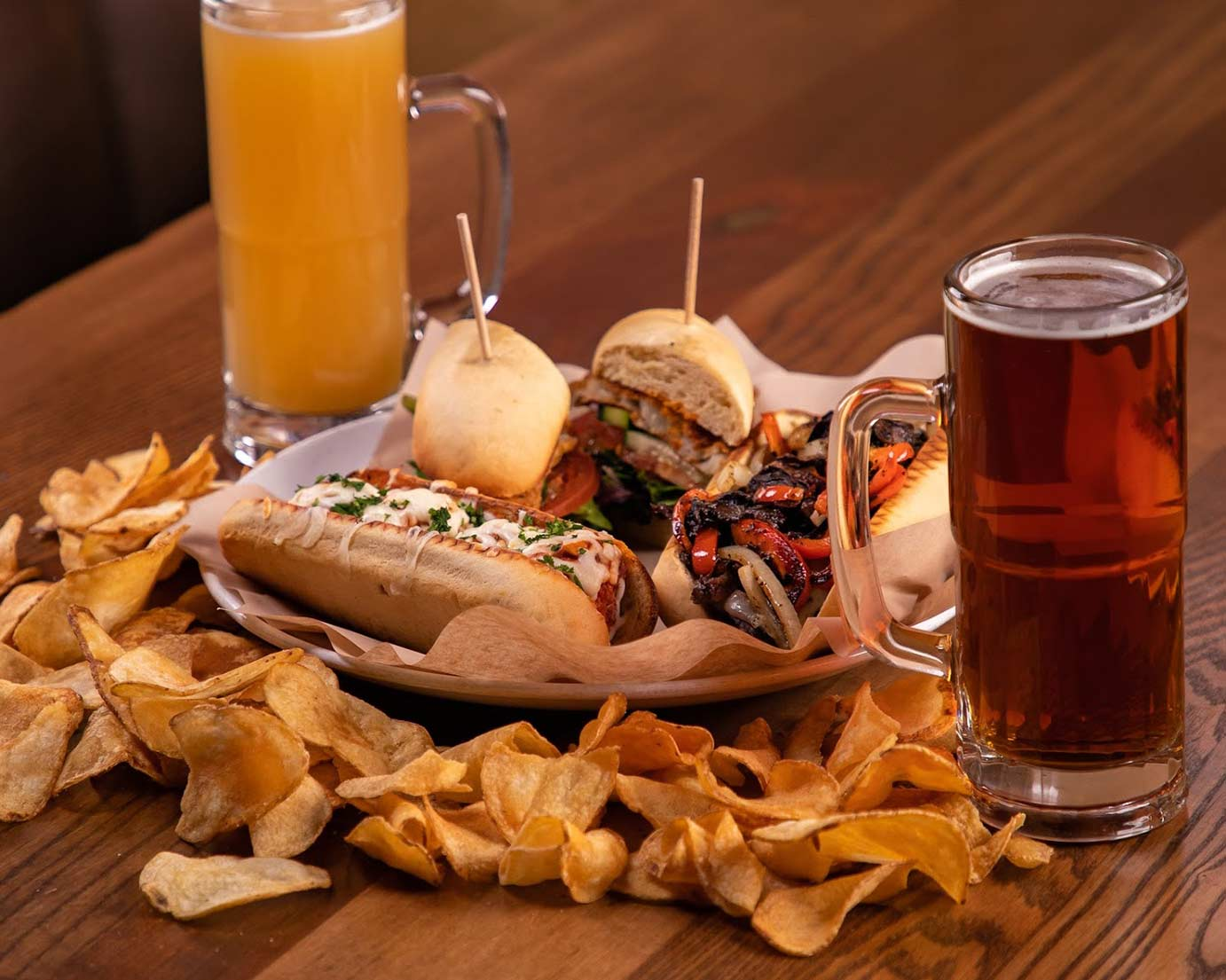 Four sandwiches and two mugs of beer, potato chips around a plate