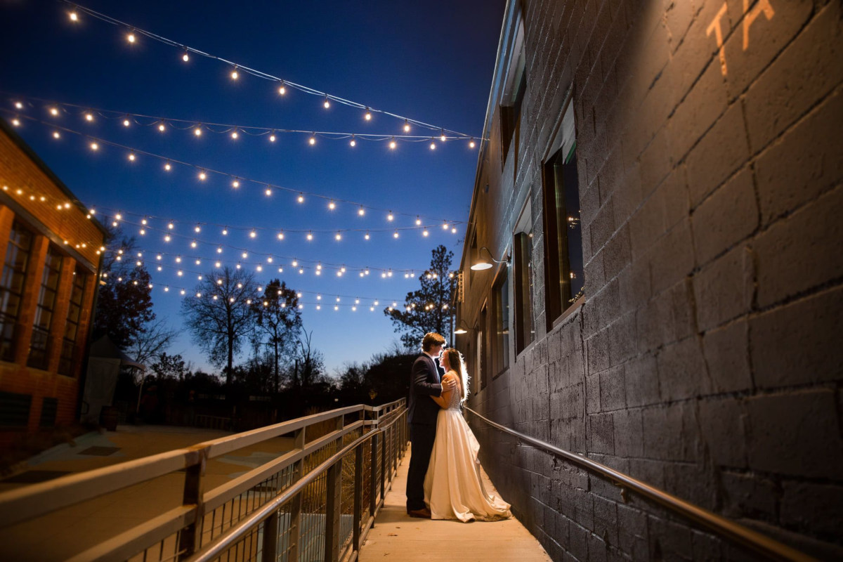 Exterior, night, bride and groom posing for a photo